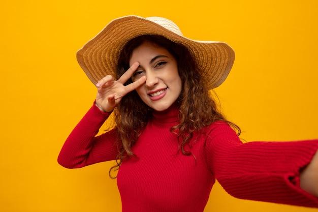 Jonge, mooie vrouw met een rode coltrui in een zomerhoed die er gelukkig en vrolijk uitziet en breed glimlacht met een v-teken