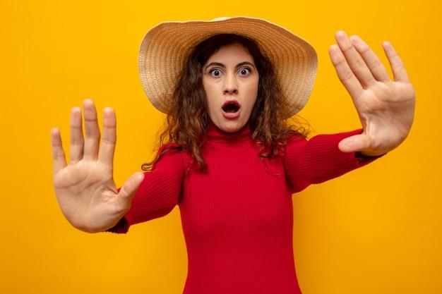 Jonge, mooie vrouw met een rode coltrui in een zomerhoed die zich zorgen maakt over het maken van een stopgebaar met handen die over de oranje muur staan