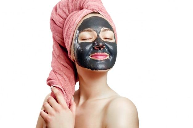 Jonge mooie vrouw met een roze handdoek op haar hoofd maakt een gezichtsmasker en glimlacht