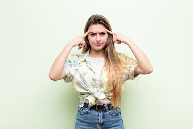 Jonge mooie vrouw met een serieuze en geconcentreerde blik, brainstormend en denkend aan een uitdagend probleem
