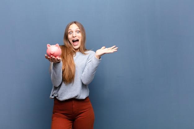 Jonge mooie vrouw met een spaarvarken tegen blauwe muur met een exemplaarruimte