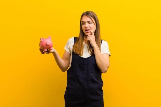 Jonge mooie vrouw met een spaarvarken tegen oranje achtergrond