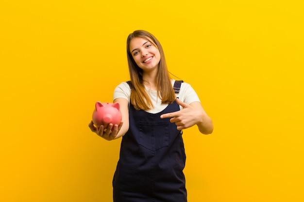 Jonge mooie vrouw met een spaarvarken tegen sinaasappel