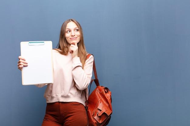 Jonge mooie vrouw met een stuk papier tegen blauwe muur met een copyspace
