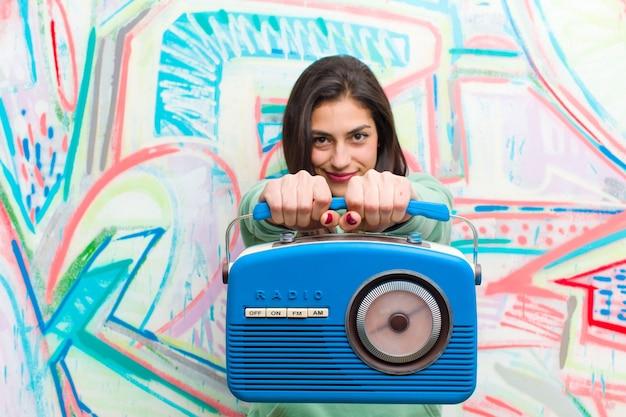 Jonge mooie vrouw met een vintage radio graffitimuur