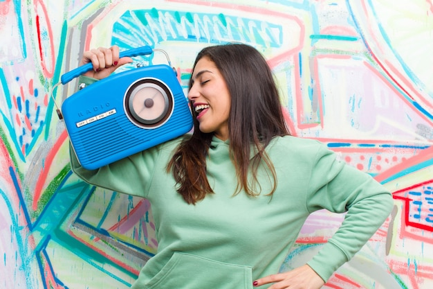 Jonge mooie vrouw met een vintage radio tegen graffitimuur