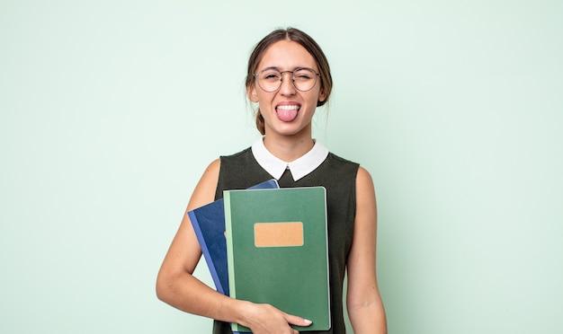 Jonge mooie vrouw met een vrolijke en opstandige houding, een grapje en tong uitsteekt. universitair concept