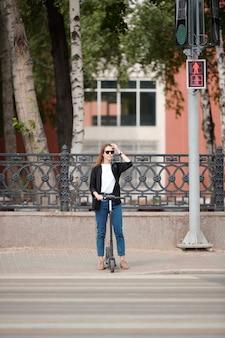 Jonge mooie vrouw met elektrische scooter staan bij verkeerslichten en wachten op het groene licht om de weg over te steken terwijl ze zich haasten naar het werk