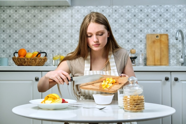 Jonge mooie vrouw met fruit in de keuken, meisje aan tafel zitten en sinaasappel snijden. vrouwelijke foodblogger die fruitsalade kookt voor de camera