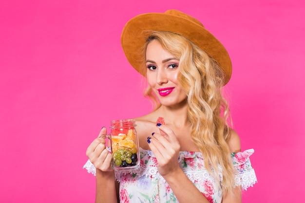 Jonge mooie vrouw met fruitkruik op roze muur