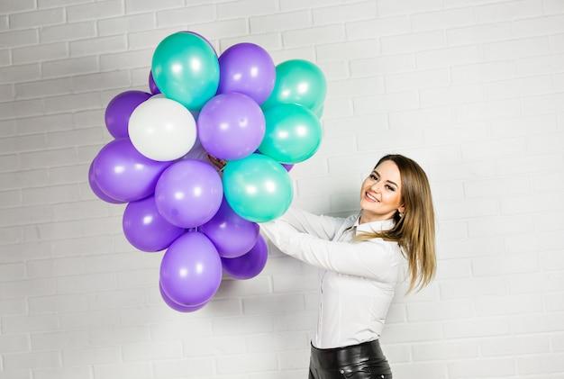 Jonge mooie vrouw met gekleurde ballonnen
