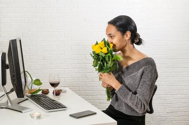 Jonge mooie vrouw met gemengd ras houdt een bos gele rozen voor haar gezicht