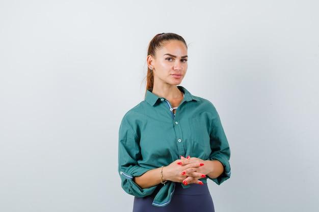Jonge mooie vrouw met gevouwen handen voor haar in groen shirt en zelfverzekerd, vooraanzicht.