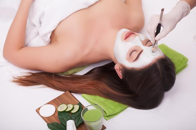 Jonge mooie vrouw met gezichtsmasker, kuuroordbehandeling