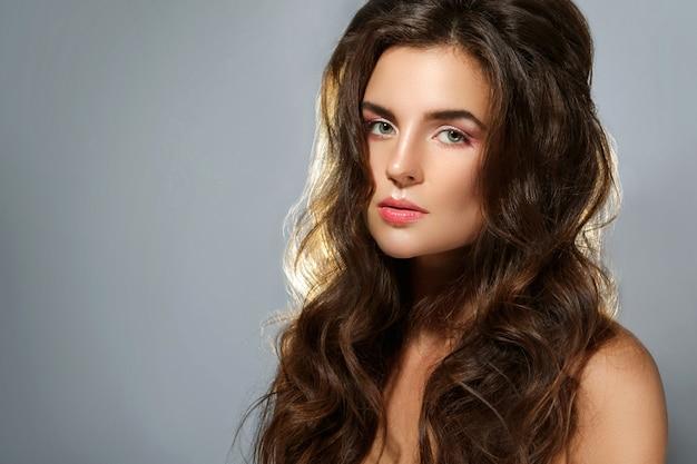 Jonge mooie vrouw met gezond, mooi en krullend haar