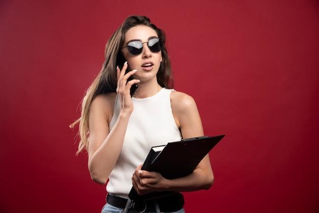 Jonge mooie vrouw met glazen die op telefoon spreken en notitieboekjes houden