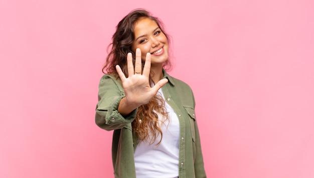 Jonge mooie vrouw met groen denim open hemd poseren op roze muur
