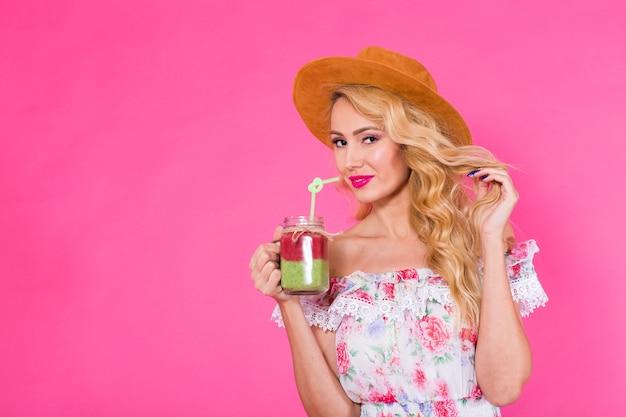 Jonge mooie vrouw met groene smoothie op roze achtergrond met copyspace