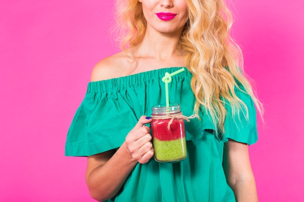 Jonge mooie vrouw met groene smoothie op roze achtergrond.