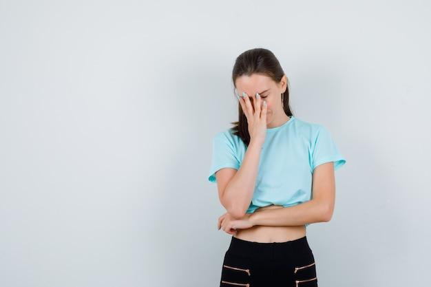 Jonge mooie vrouw met hand op gezicht in t-shirt, broek en teleurgesteld, vooraanzicht.