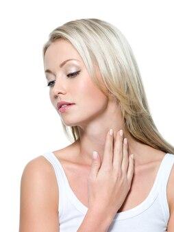 Jonge mooie vrouw met hand op hals - witte ruimte