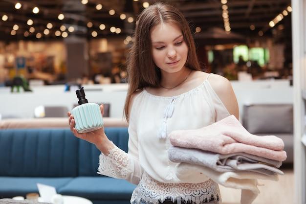 Jonge mooie vrouw met handdoeken in een winkel