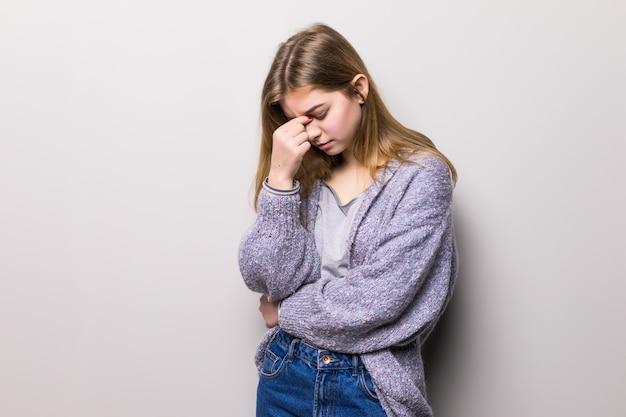 Jonge mooie vrouw met hoofdpijn die op grijze muur wordt geïsoleerd.
