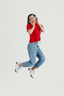 Jonge mooie vrouw met hoofdtelefoons springen Premium Foto