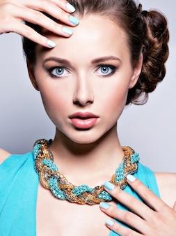 Jonge mooie vrouw met juwelen. meisjesmanier in blauwe kleding die bijouterie draagt. aantrekkelijk model met blauwe nagels.