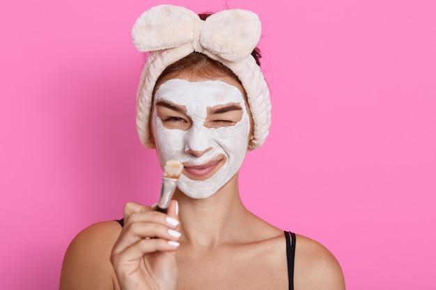 Jonge mooie vrouw met klei gezichtsmasker op haar borstel van de gezichtsholding in handen na het doen van schoonheidsbehandeling, die grappig gezicht maken terwijl de huidmanipulatie doet, thuis hebbend pret.