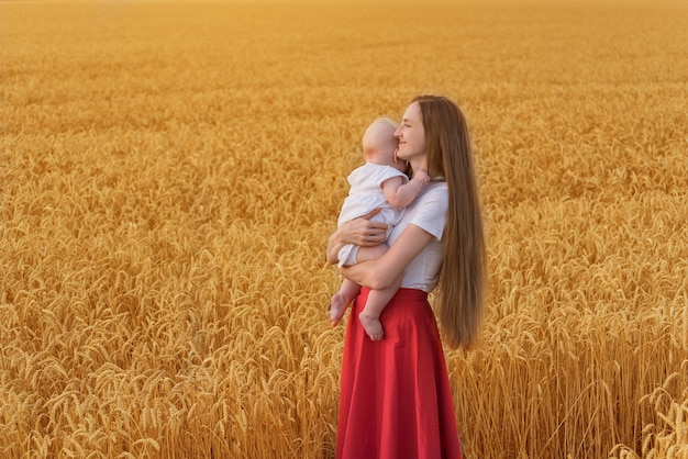 Jonge mooie vrouw met klein kind in een tarweveld