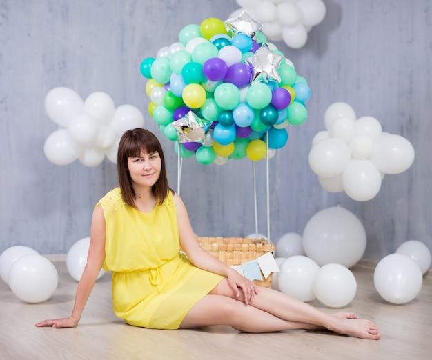 Jonge mooie vrouw met kleurrijke luchtballon en witte wolken