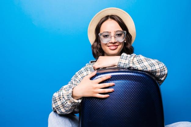 Jonge mooie vrouw met koffer met zonnebril en strooien hoed klaar voor zomervakantie