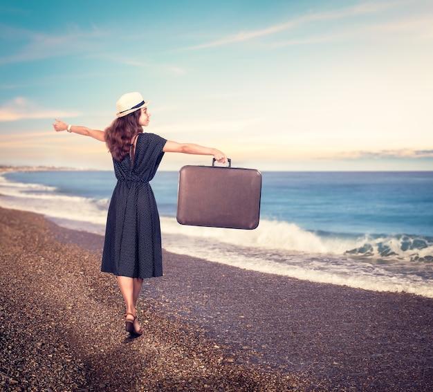 Jonge mooie vrouw met koffer op het strand.