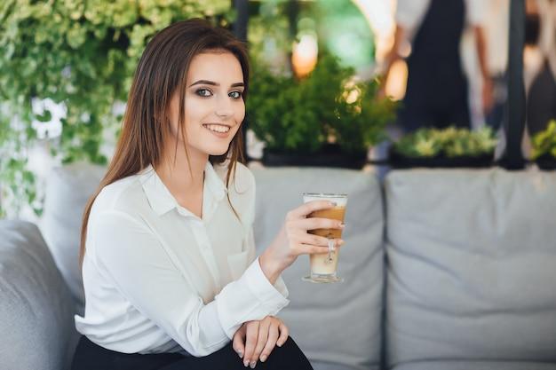 Jonge mooie vrouw met koffie in haar handen in een wit overhemd zittend op kantoor