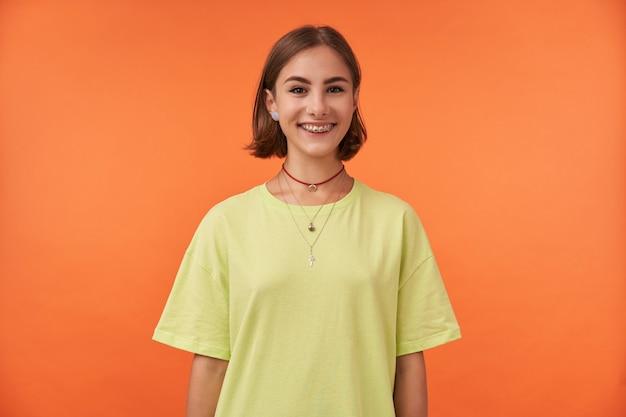 Jonge mooie vrouw met kort haar, brede glimlach, gelukkig op zoek. groen t-shirt, tandensteunen en ketting dragen.