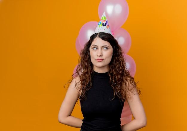 Jonge mooie vrouw met krullend haar die bos van luchtballons houden die opzij kijken met sceptisch expressin concept van de verjaardagsfeestje die zich over oranje muur bevinden