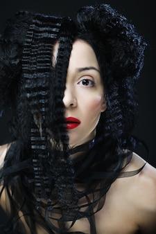 Jonge mooie vrouw met krullend haar en rode lippen