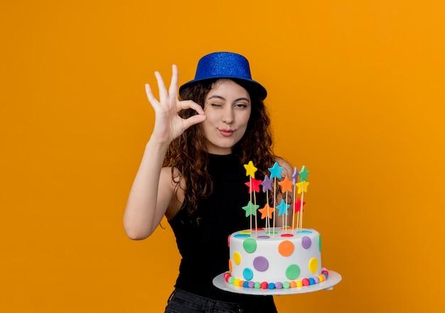 Jonge mooie vrouw met krullend haar in een de holdingsverjaardagstaart die van de vakantiehoed ok teken tonen glimlachend en knipogend status over oranje muur tonen