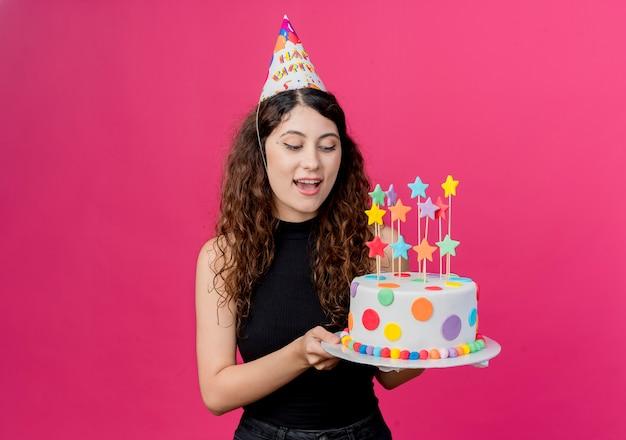 Jonge mooie vrouw met krullend haar in een vakantie glb bedrijf verjaardagstaart gelukkig en positief concept verjaardagsfeestje over roze