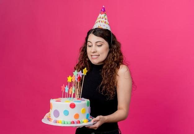 Jonge mooie vrouw met krullend haar in een vakantie glb bedrijf verjaardagstaart gelukkig en positief verjaardagsfeestje concept staande over roze muur