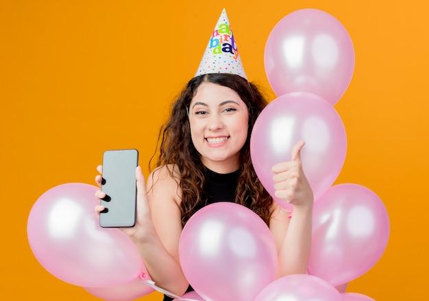 Jonge mooie vrouw met krullend haar in een vakantie glb houden lucht ballonnen en smartphone duimen opdagen, blij en opgewonden verjaardag partij concept over oranje