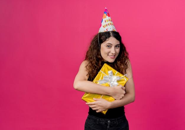 Jonge mooie vrouw met krullend haar in een vakantie glb met de doos van de verjaardagsgift die vrolijk het concept van de verjaardagspartij glimlachen die zich over roze muur bevinden