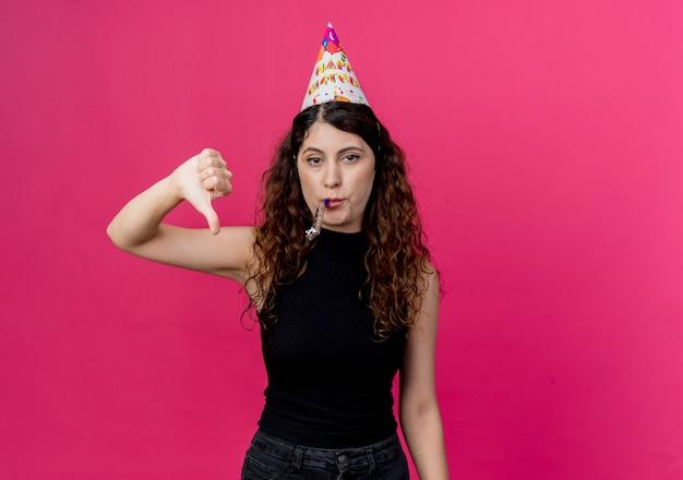 Jonge mooie vrouw met krullend haar in een vakantie glb waait fluitje ontevreden tonen duimen omlaag verjaardagsfeestje concept over roze