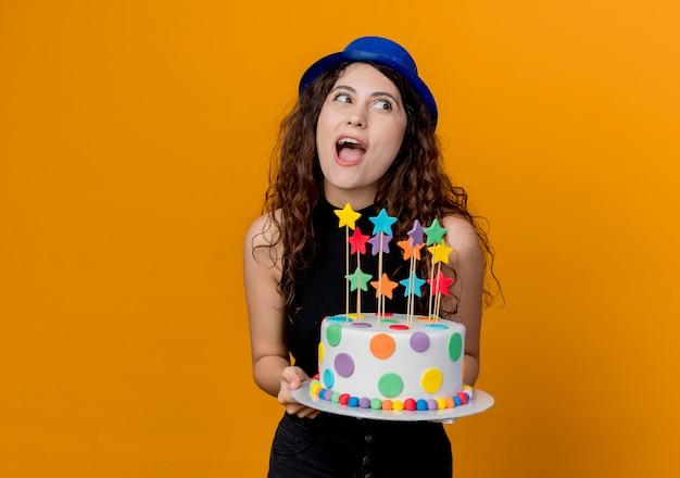 Jonge mooie vrouw met krullend haar in een vakantiehoed met verjaardagstaart blij en verrast staande over oranje muur