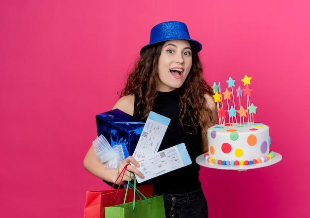 Jonge mooie vrouw met krullend haar in een vakantiehoed met verjaardagstaart geschenkdoos en vliegtickets blij en opgewonden verjaardagsfeestje concept staande over roze muur
