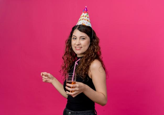Jonge mooie vrouw met krullend haar in een vakantiepet met cocktail het gelukkige en glimlachende concept van de verjaardagspartij die zich over roze muur bevinden