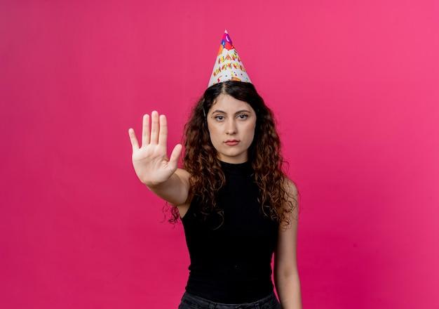 Jonge mooie vrouw met krullend haar in een vakantiepet met ernstig gezicht die het concept van de de verjaardagspartij van het stopbord maken die zich over roze muur bevinden