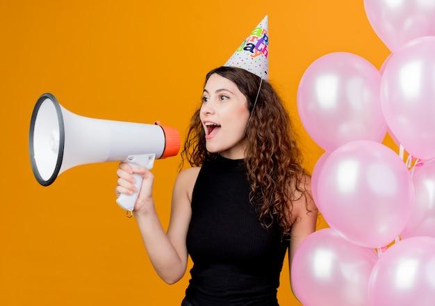 Jonge mooie vrouw met krullend haar in een vakantiepet met luchtballons die naar megafoon schreeuwen blij en opgewonden verjaardagsfeestje concept staande over oranje muur