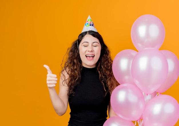 Jonge mooie vrouw met krullend haar in een vakantiepet met luchtballons gek gelukkig duimen opdagen verjaardagsfeestje concept staande over oranje muur